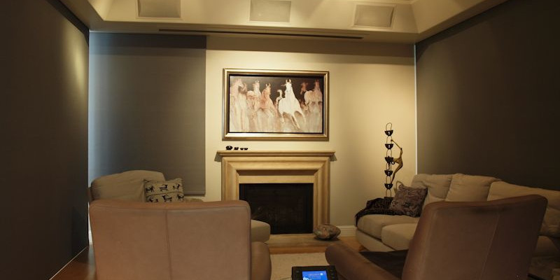 Marin Custom Home Theater-Showing a picture of the art work hiding the plasma with two of the light block shades rolled down. Controlled by the Crestron touch panel on the table.