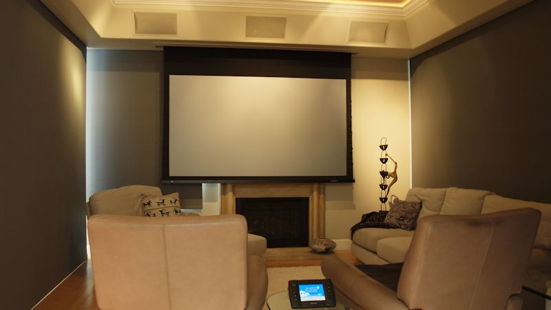 Marin Custom Home Theater-Showing a picture of all the light block shades down and the projection screen dropped in front of the Plasma TV.  Controlled by the Crestron touch panel on the table.